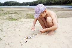 使用在与壳的海滩的逗人喜爱的男孩 免版税库存照片