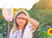 使用在与昆虫网的一个领域的快乐的小女孩 免版税图库摄影