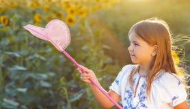使用在与昆虫网的一个领域的快乐的小女孩 库存图片