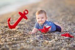 使用在与海红色星和船锚的海滩的逗人喜爱的小孩男孩 免版税库存照片
