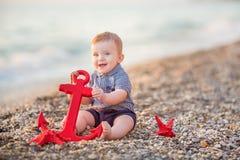 使用在与海红色星和船锚的海滩的逗人喜爱的小孩男孩 免版税库存图片