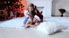 使用在与礼物的一棵圣诞树附近的母亲和小孩 在家平衡舒适的冬天 xmas 新年好 影视素材
