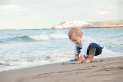 使用在与船的海滩的Litlle男孩 暑假和 免版税库存照片