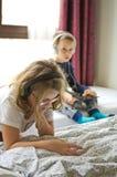 使用在与他们的片剂和电话的床上的孩子 图库摄影