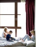 使用在与他们的片剂和电话的床上的孩子 免版税图库摄影