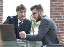 使用在业务会议的膝上型计算机的两个商人在办公室 库存照片