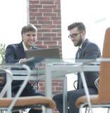 使用在业务会议的膝上型计算机的两个商人在办公室 免版税图库摄影