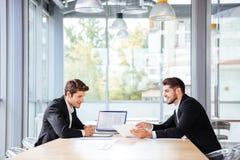 使用在业务会议的膝上型计算机的两个愉快的商人 免版税库存图片