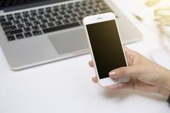 使用在书桌上的一个白色巧妙的电话关闭妇女手 库存图片