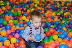 使用在五颜六色的塑料球操场的愉快的小孩 免版税库存照片