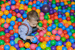 使用在五颜六色的塑料球操场的愉快的小孩 图库摄影