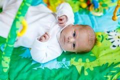 使用在五颜六色的玩具健身房的逗人喜爱的可爱的新出生的婴孩 免版税图库摄影