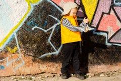 使用在五颜六色的街道画前面的年轻男孩 免版税库存照片