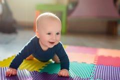 使用在五颜六色的软的席子的婴儿男婴 做首先爬行的小孩在地板上跨步 顶视图从上面 免版税库存图片