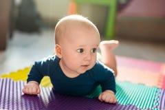 使用在五颜六色的软的席子的婴儿男婴 做首先爬行的小孩在地板上跨步 顶视图从上面 图库摄影