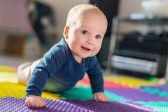 使用在五颜六色的软的席子的婴儿男婴 做首先爬行的小孩在地板上跨步 顶视图从上面 免版税图库摄影
