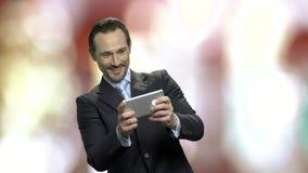 使用在他的智能手机的激动的中年商人 影视素材