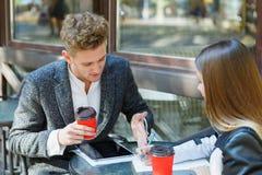 使用在会议的两个年轻商人数字式片剂在咖啡店 免版税图库摄影