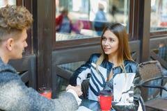 使用在会议的两个年轻商人数字式片剂在咖啡店 免版税库存图片