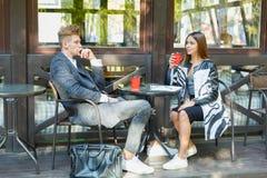 使用在会议的两个年轻商人数字式片剂在咖啡店 库存图片