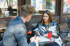 使用在会议的两个年轻商人数字式片剂在咖啡店 图库摄影