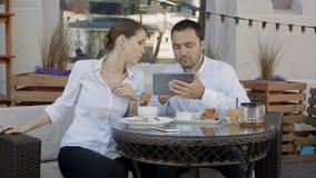 使用在会议的两个年轻商人数字式片剂在咖啡店 股票视频