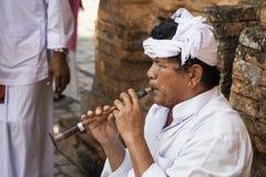 使用在传统木长笛的白色衣裳的音乐家 免版税库存图片