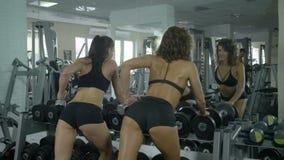 使用在健身房的一个哑铃,一种健康生活方式,两位美丽的性感的教练员运动员训练手的肌肉 股票录像