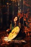 使用在僧人在背景的框架鼓的美丽的shamanic女孩与叶子和花 免版税图库摄影
