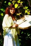 使用在僧人在自然的框架鼓的美丽的shamanic女孩 免版税库存图片