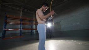 使用在全国巴西仪器berimbau的一个运动人在做capoeira元素以后在屋子里与 股票视频