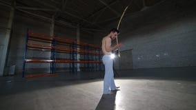 使用在全国巴西仪器berimbau的年轻运动人在做capoeira元素以后在屋子里与 影视素材