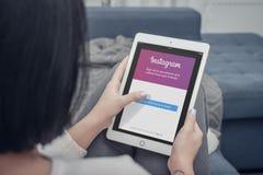 使用在全新的苹果计算机iPad赞成银的妇女Instagram app 免版税库存图片