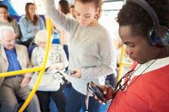 使用在公共汽车旅途上的乘客移动设备 免版税库存图片