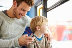 使用在公共汽车旅途上的父亲手机与儿子 免版税库存图片