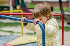 使用在公园室外乘驾的救生服婴孩的小迷人的女孩,乘坐在跷跷板 免版税库存图片