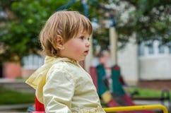 使用在公园室外乘驾的救生服婴孩的小迷人的女孩,乘坐在跷跷板 库存照片