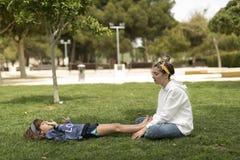 使用在公园的两个姐妹坐草 免版税库存照片