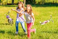 使用在公园的两个愉快的小女孩 库存照片