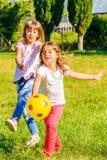 使用在公园的两个愉快的小女孩 免版税库存图片