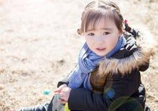 使用在公园的可爱的矮小的亚裔女孩 免版税库存照片