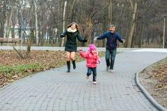 年轻使用在公园的家庭母亲父亲小婴孩 库存照片