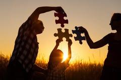 使用在公园的愉快的家庭在日落时间 免版税库存照片