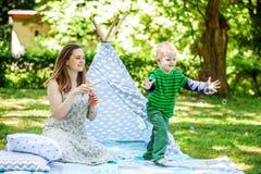 使用在公园的母亲和小儿子 泡影 作为背景诱饵概念美元灰色吊异常分支 免版税库存照片