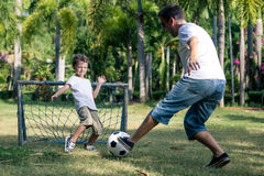 使用在公园的父亲和儿子在天时间 图库摄影