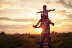 使用在公园的父亲和儿子在日落时间 免版税图库摄影