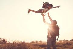 使用在公园的父亲和儿子在日落时间 免版税库存照片