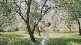 使用在公园的父亲和儿子 父亲培养胳膊的孩子并且投掷  股票视频