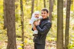 使用在公园的爸爸和新出生的女儿在秋天 免版税库存照片