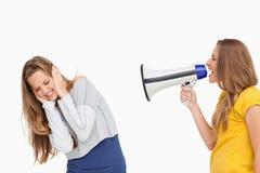使用在其他女孩的白肤金发的学员一台扩音器 免版税库存照片